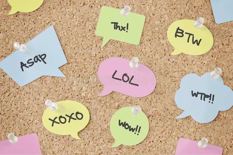 Speech bubbles with chat abbreviations on pinboard. Speech bubbles with chat abbreviations on cork pinboard royalty free stock images