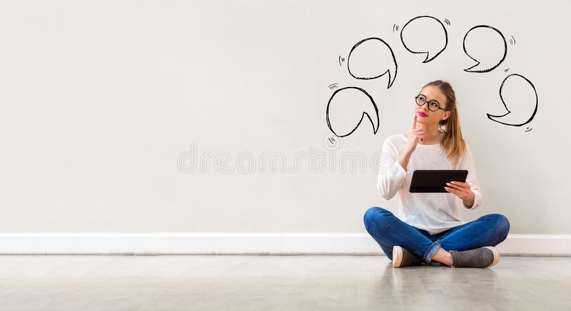 Speech bubbles with woman using a tablet royalty free stock photos