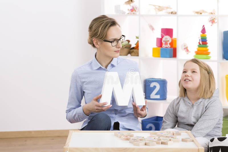 Speech therapist helping little girl royalty free stock photos