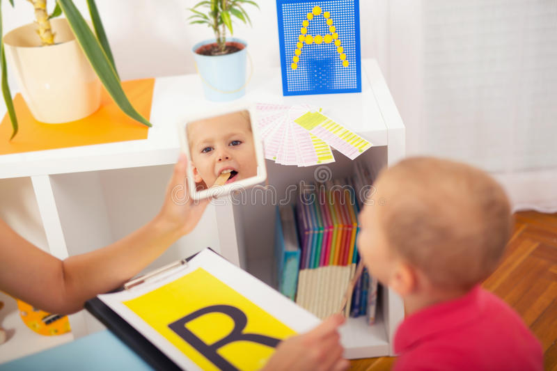 Speech therapist teaches the boys to say the letter R. Speech therapist teaches the little boys to say the letter R royalty free stock images