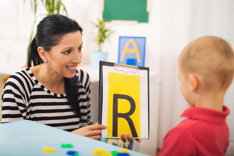 Speech therapist teaches the boys to say the letter R. Speech therapist teaches little boys to say the letter R stock photography