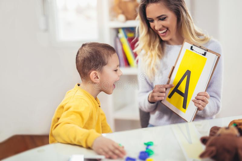 Speech therapist teaches the boys to say the letter A. Smiling speech therapist teaches the boys to say the letter A stock photography