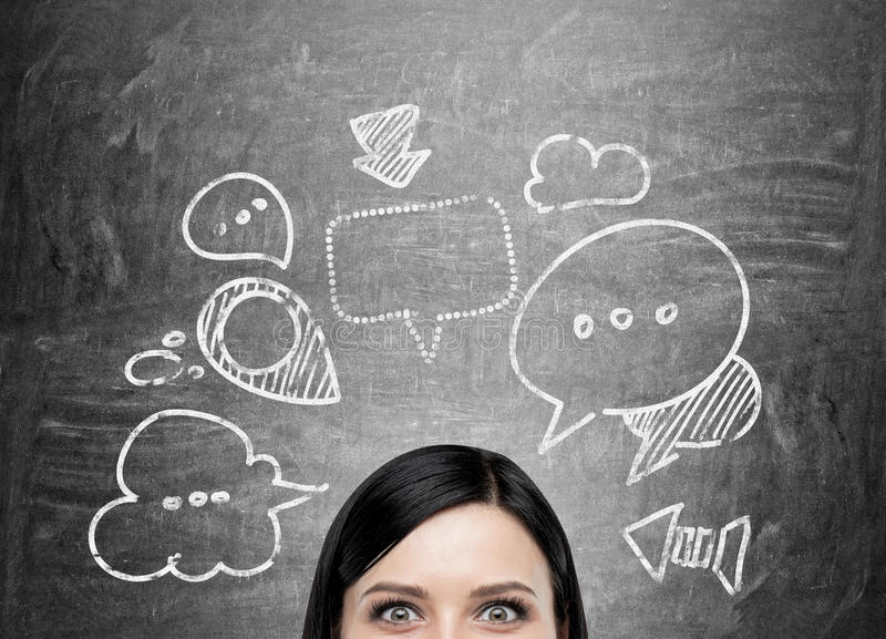 Speech and thought bubbles. Businesswoman with speech and thought bubbles on chalkboard royalty free stock photos