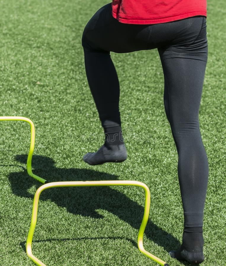Speed and agility drills over yellow mini hurdles with no shoes. A high school track athlete is not wearing shoes while performing speed and agility drills in stock image