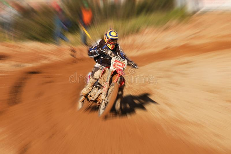 Speed blurred photography of motocross racer 2 coming off turn during finals royalty free stock image