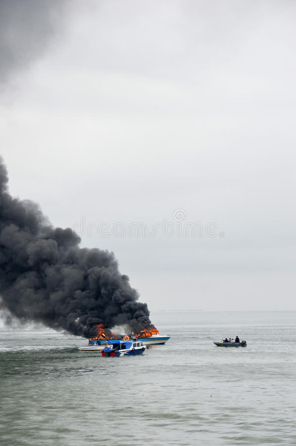 Speed boat on fire in Tarakan, Indonesia. TARAKAN, INDONESIA - Oct 31 : a speedboat carrying passengers between islands on fire during refueling on Oct 31, 2013 stock images
