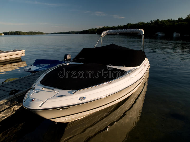 Speed Boat. Half covered speed boat at sunrise at a wooden dock royalty free stock photos