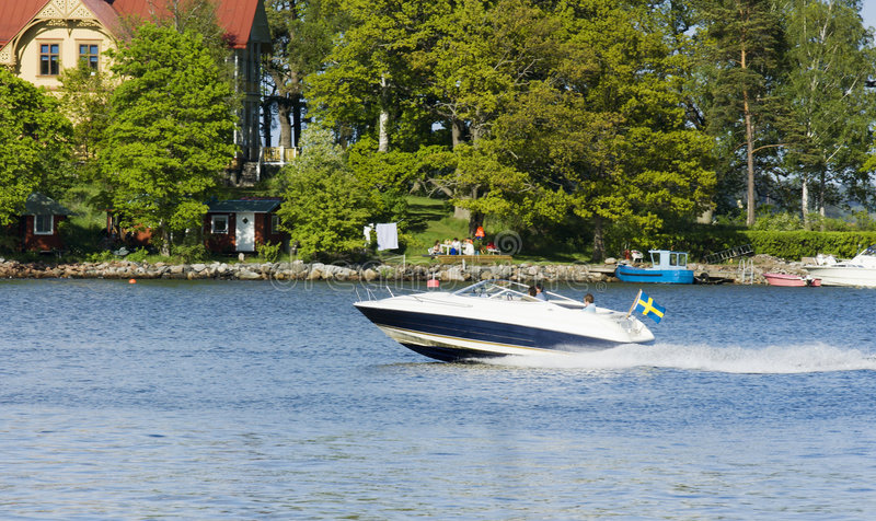 Speed-boat and island. Speed-boat in-front of island with people and boats royalty free stock photo