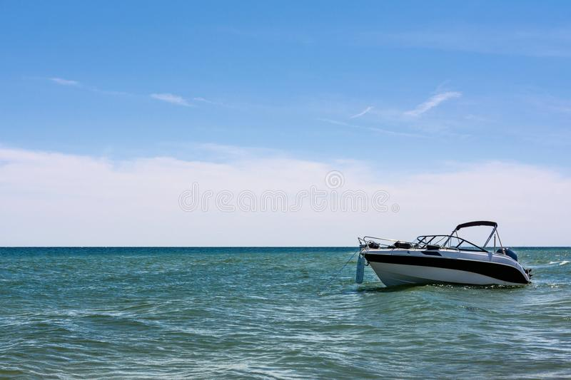 Speed boat at the seaside. Vacation concept - empty white speed boat on seaside on blue sky background royalty free stock image