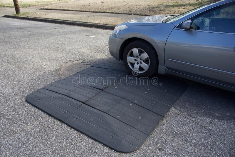 Car Riding Over Speed Bump in Residential Area. Speed bumps are the common name for a family of traffic calming devices that use vertical deflection to slow stock photography