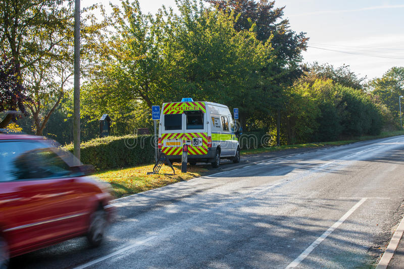 Speed camera and passing car. Car passing a mobile speed camera in village royalty free stock images