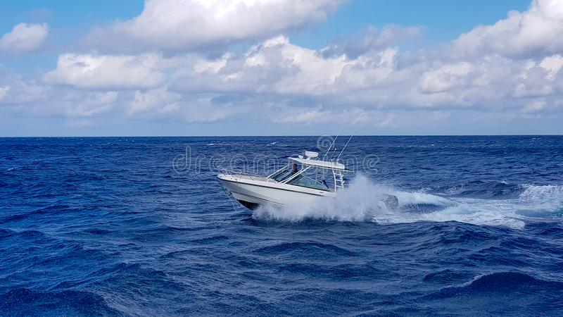 Speed fishing tender boat jumping the waves in the sea and cruising the blue ocean day in Bahamas. Blue beautiful water. Speed fishing tender boat jumpling the royalty free stock image