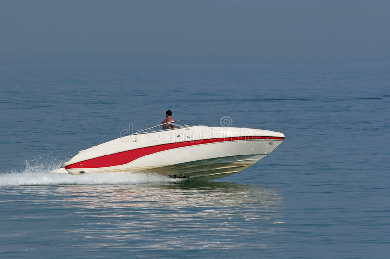 Speed Freak. Man in a powerful white and red speed boat on the sea royalty free stock photo