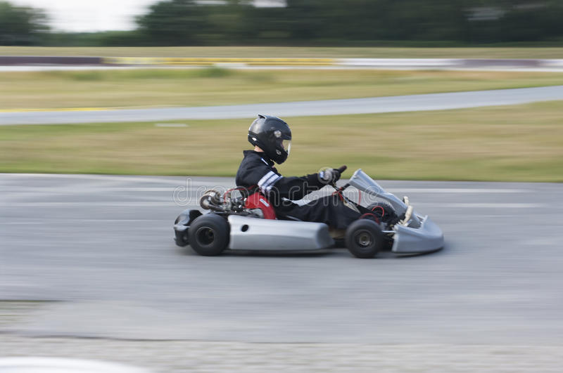 At the Speed Limit. A professional kart driver speeds away royalty free stock photography