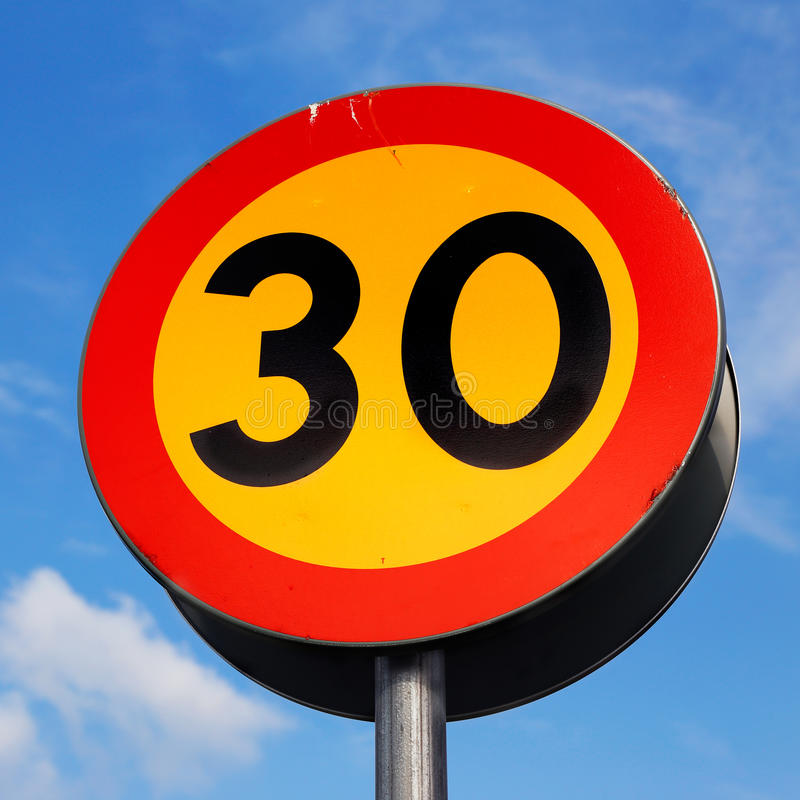Speed limit 30 km/h. Swedish road sign with black letters on a yellow background with red frame against blue sky indicates that the speed is limited to a maximum royalty free stock image