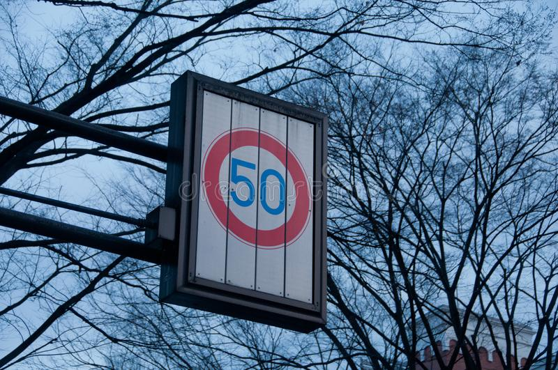 Speed limit at 50 kmph traffic sign with dried tree branches. In Winter royalty free stock photo