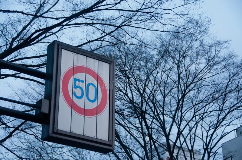 Speed limit at 50 kmph traffic sign with dried tree branches. In Winter stock photo