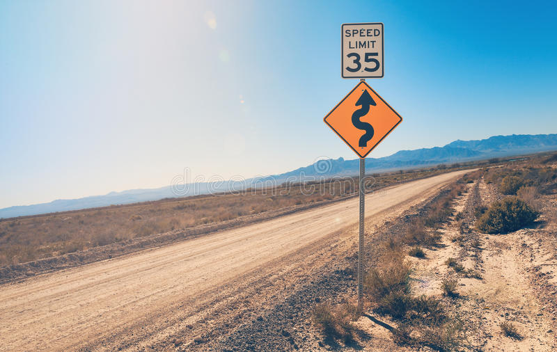 Speed Limit Sign and Curve Sign in desert royalty free stock image
