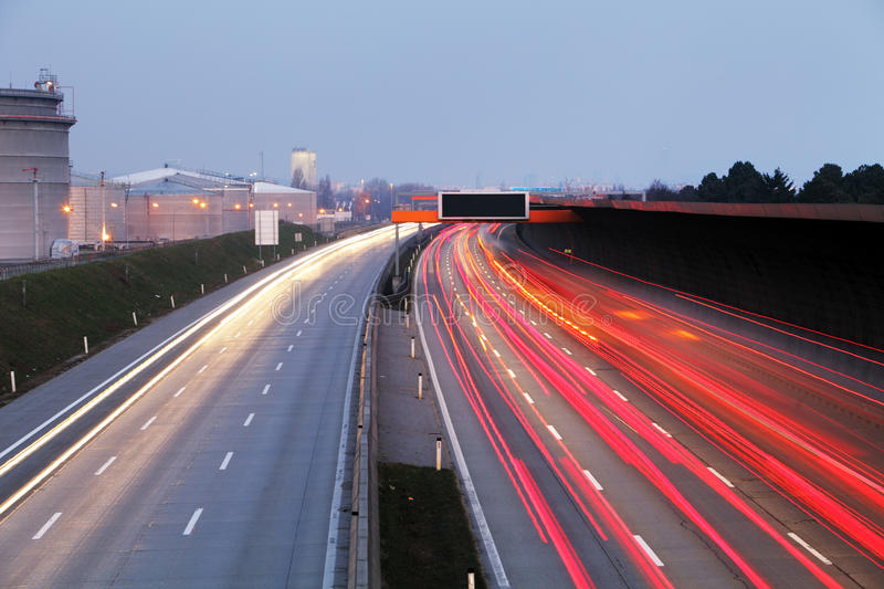 Speed Traffic at Dramatic Sundown Time - light trails on motorway highway at night, long exposure abstract urban background stock image