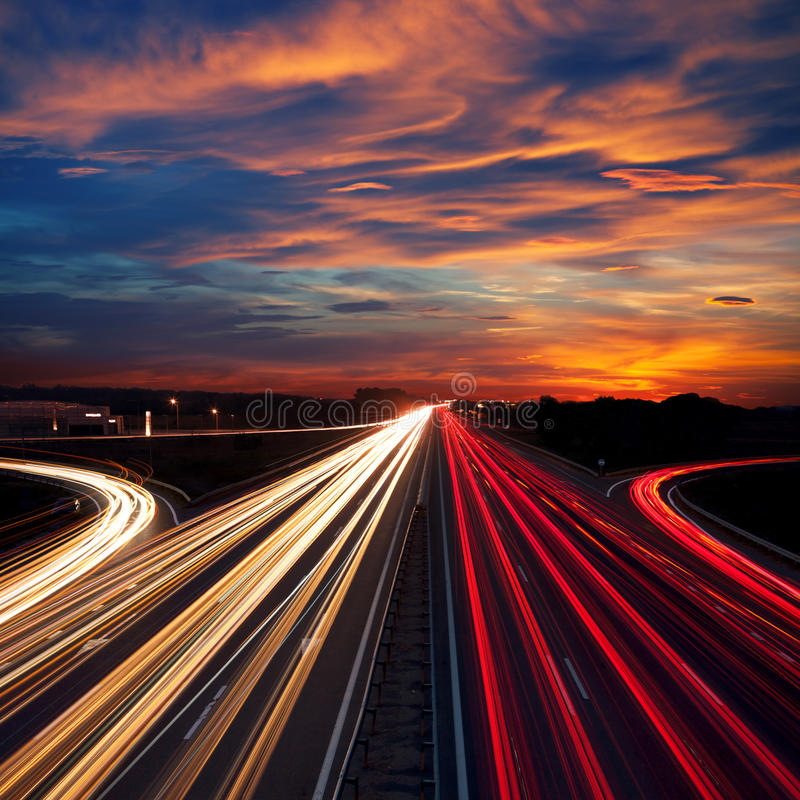 Speed Traffic at Dramatic Sundown Time - light trails. On motorway highway at night, long exposure abstract urban background royalty free stock images