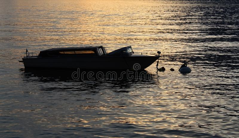 Speedboat in the shadow on a lake at sunset royalty free stock images