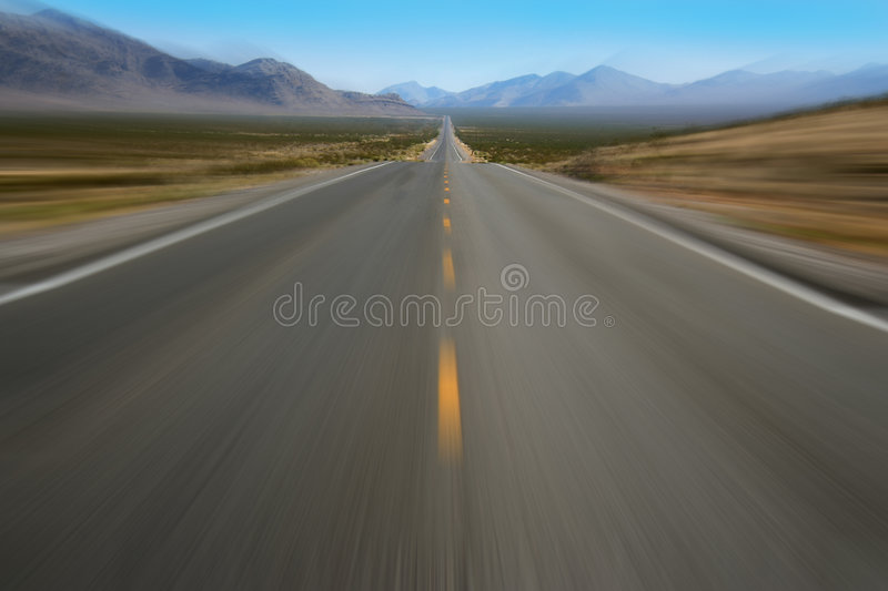 Speeding. Down an empty desert highway royalty free stock photos