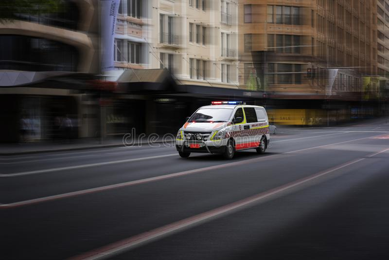 Speeding ambulance during emergency. A speeding ambulance heads south through the city of Sydney after an emergency call stock photo