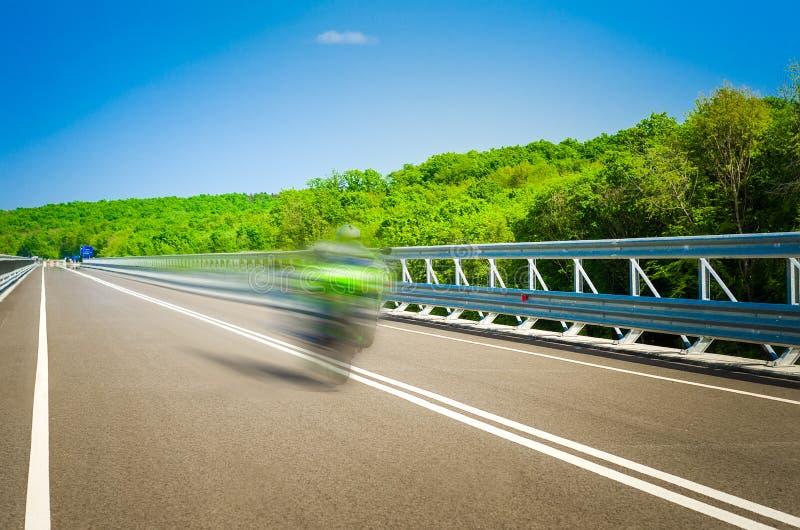 Speeding bike on a straight road royalty free stock photo