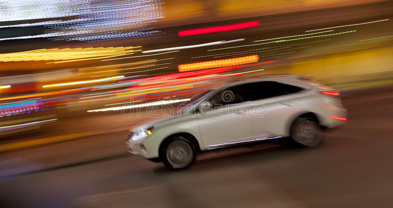 Speeding Car. Car speeding at night with blurred lights. Panning shot to show motion stock image