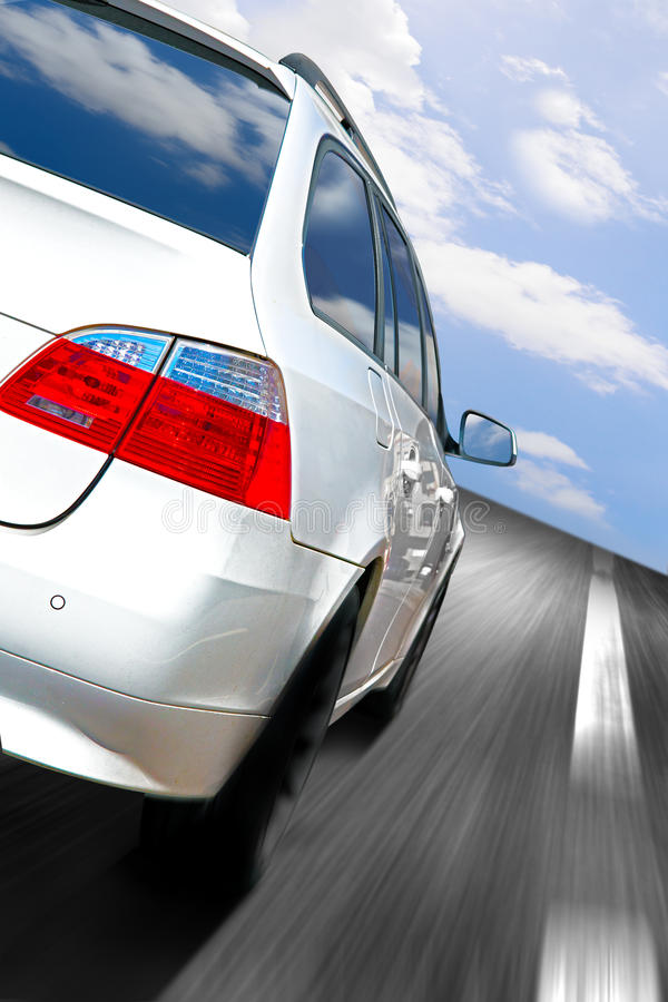Car speeding. White car speeding on the highway under a beautiful cloudy sky stock photo