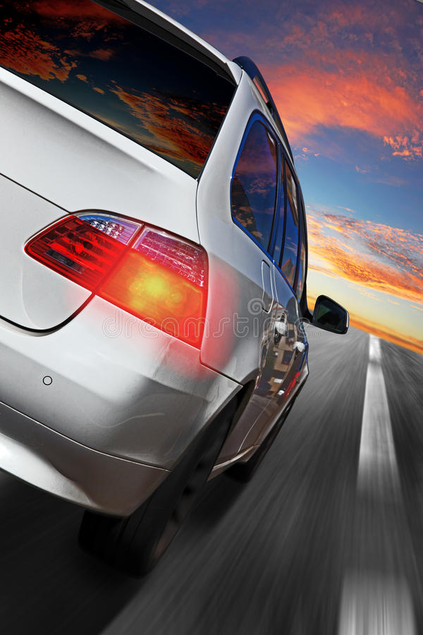 Car speeding. Back view of a white car speeding on the highway under a beautiful sunset cloudy sky stock images