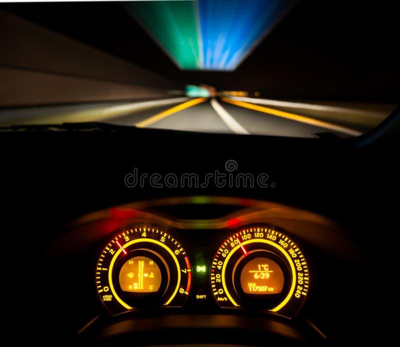 Speeding car dashboard. Driver view at speeding car dashboard and motorway at night royalty free stock photo