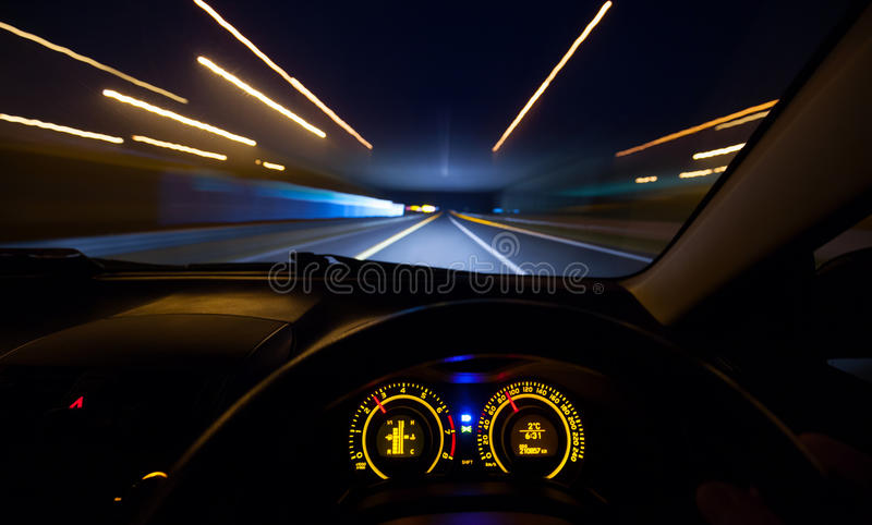Speeding car dashboard. Driver view at speeding car dashboard and motorway at night stock photography