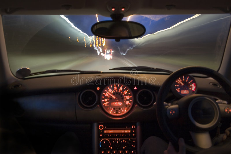 Speeding car at night. Interior shot of the lit up dashboard and screen of a british car travelling at speed at night