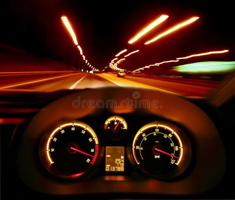 Speeding car at night. Speeding road racer car at night with illuminated dashboard and dials and speed blur royalty free stock photo