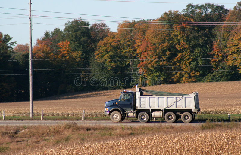 Speeding Dump Truck. A dump truck speeding on a road during the harvest stock images
