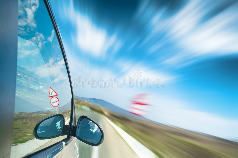 Speeding on the highway. Car speeding on the highway on a sunny day stock photo