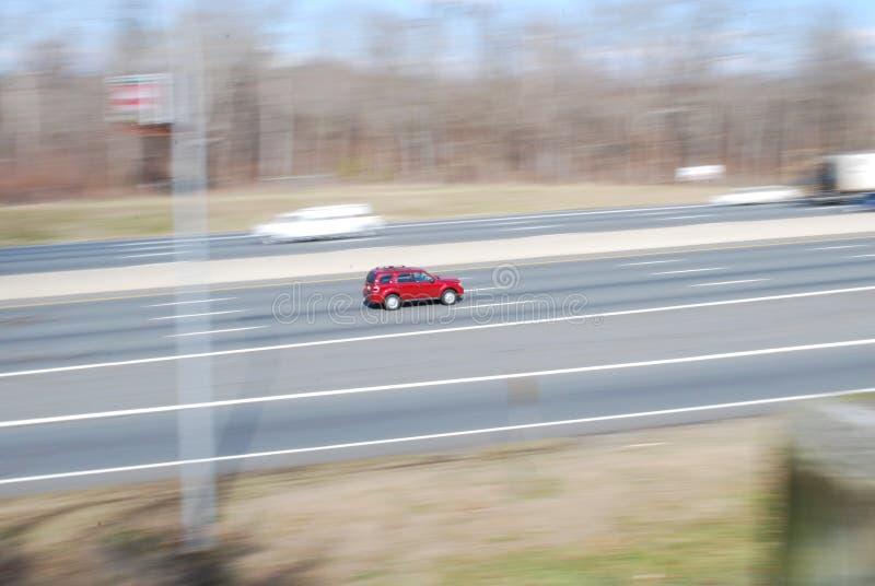 Speeding red car rushing down highway stock photos