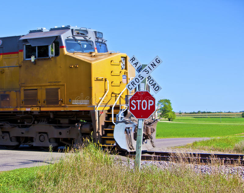 Speeding train. A speeding train crossing a road in rural America stock image
