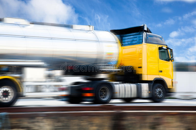 Speeding truck. Yellow fast tanker truck with motion blur