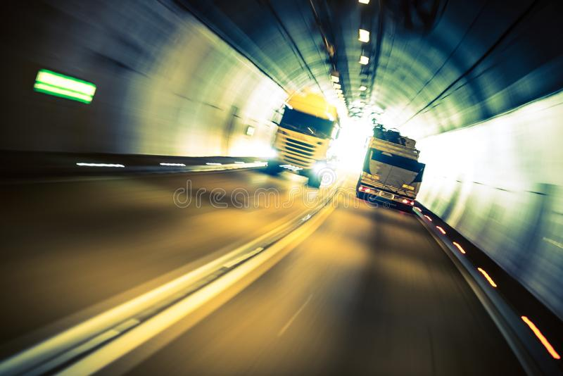 Speeding Trucks in the Tunnel. Trucking Road Transportation stock images