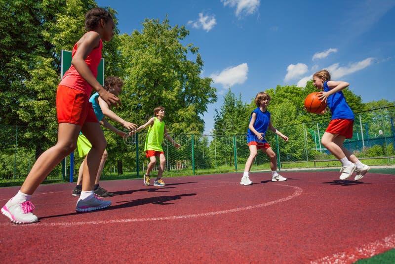Speel het basketbalspel van het tienersteam samen stock afbeeldingen