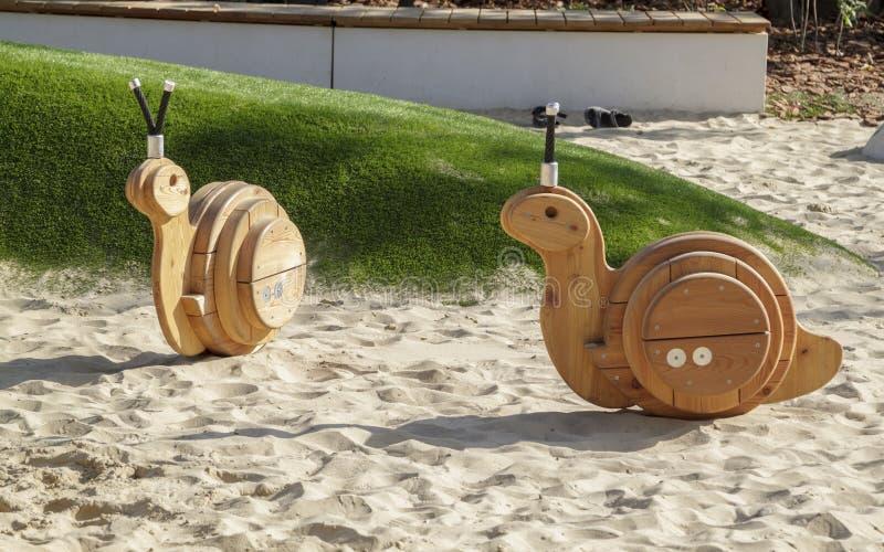 speelgoed van een schommelstoel in de vorm van slakken op een moderne Speelplaats met het behandelen van zand stock afbeeldingen