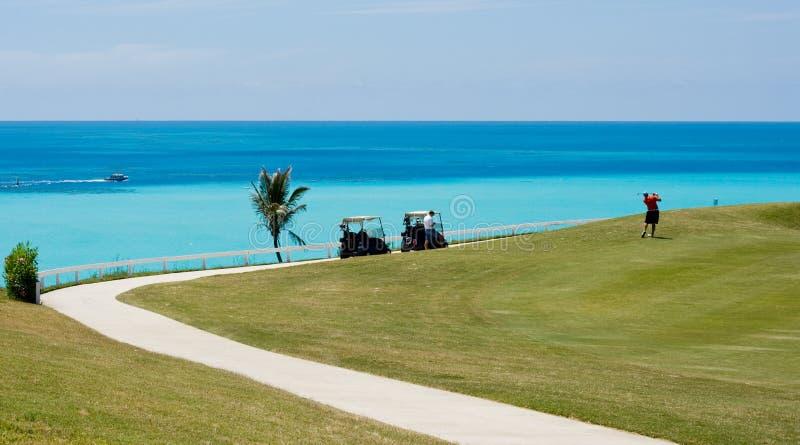 Speelgolf op een tropische golfcursus, over het kijken de oceaan stock afbeeldingen