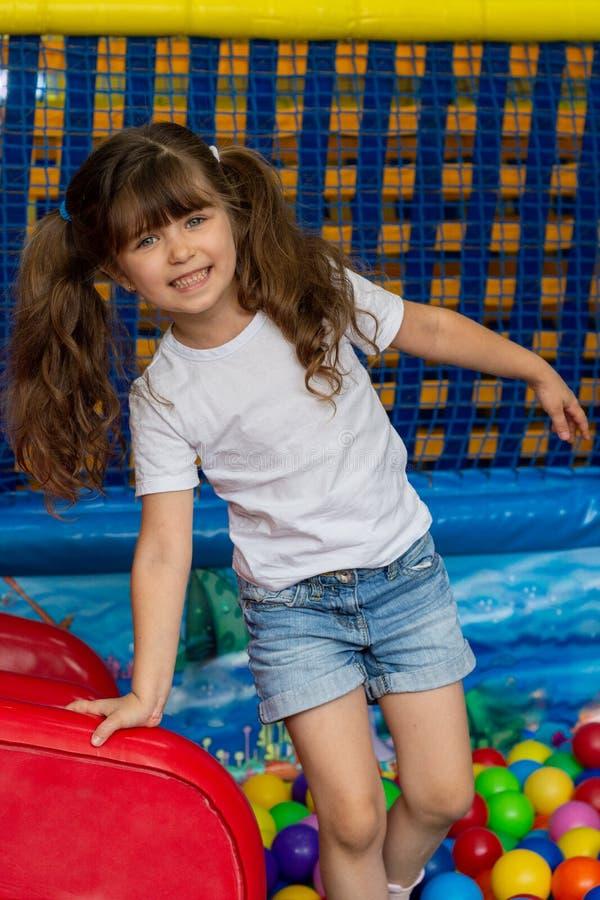 Speelplaats met balkuil binnen Blij jong geitje die pret hebben op binnenspelcentrum Kind het spelen met kleurrijke ballen in spe stock fotografie