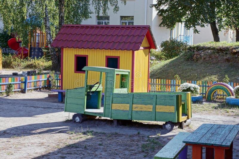 Speelplaats met een groene houten auto en een plattelandshuisje stock afbeelding
