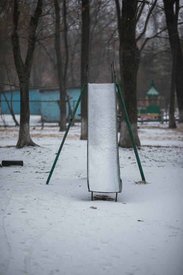 Speelplaats met sneeuw wordt behandeld die stock fotografie