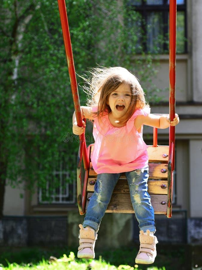 Speelplaats in Park Het kleine jong geitje spelen in de zomer Gelukkig lachend kindmeisje op schommeling romantisch meisje op de  stock afbeelding
