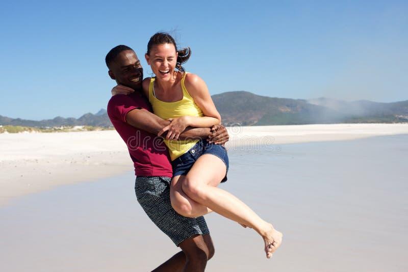 Speels jong paar die pret in openlucht op het strand hebben stock foto's