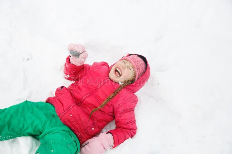 Speels meisje die met vlechten in de eerste sneeuw spelen stock afbeelding